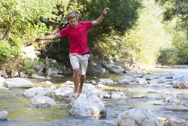 Austria, Salzkammergut, Mondsee, young man crossing a brook - WWF003200