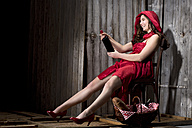 Young woman sitting in a shack dressed as Red Riding Hood, studio shot - MAEF007585