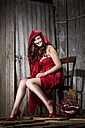 Young woman sitting in a shack dressed as Red Riding Hood, studio shot - MAEF007589