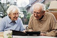 Senior couple watching old photographs at home - BIF000268