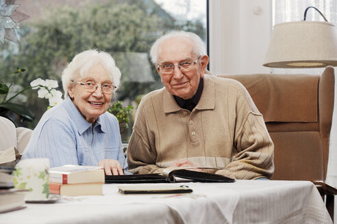 Senior couple watching old photographs at home - BIF000272