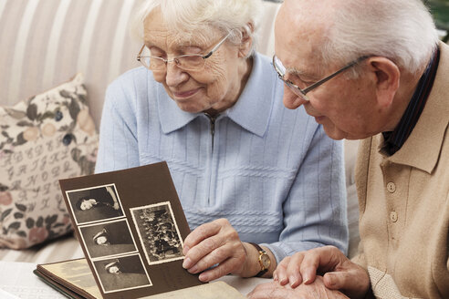 Senior couple watching old photograph album at home - BIF000274