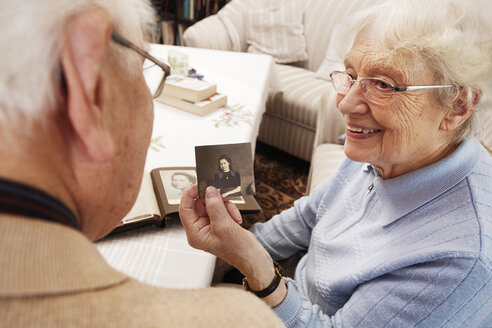Senior woman showing her husband old photograph of herself - BIF000277