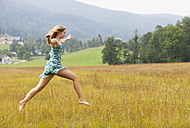 Austria, Salzkammergut, Mondsee, young woman jumping in a meadow - WWF003168