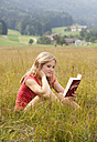 Austria, Salzkammergut, Mondsee, young woman reading book in a meadow - WWF003174