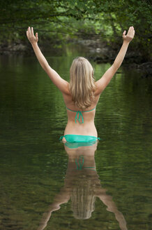 Austria, Salzkammergut, Mondsee, young woman with outstretched arms standing in a brook - WWF003185