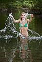 Austria, Salzkammergut, Mondsee, young woman bathing in a brook - WWF003187