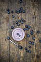 Blueberries (Vaccinium myrtillus), spoon and glass of blueberry yoghurt on wooden table - LVF000427