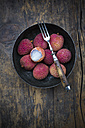 Bowl of litchis (Litchi chinensis) with fork on wooden table - LVF000422
