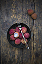Bowl of litchis (Litchi chinensis) with fork on wooden table - LVF000420