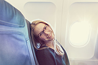 Smiling young woman in airplane, portrait - MF000726