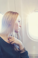 Blond young woman in airplane - MF000724