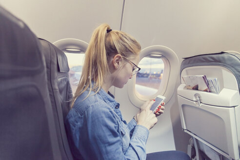 Blond young woman in airplane using smartphone - MF000731