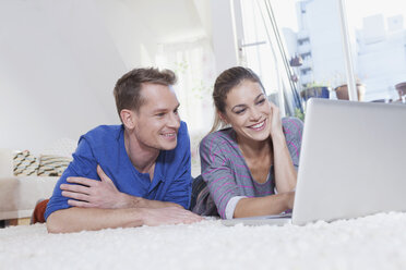 Couple at home lying on carpet and using laptop - RBF001592