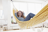 Smiling woman relaxing in a hammock in her apartment - RBF001546