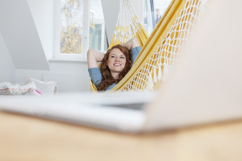 Daydreaming woman relaxing in a hammock in her apartment, laptop in front on a table - RBF001549