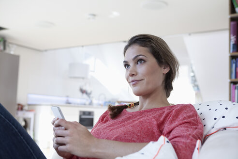 Portrait of woman sitting on a couch in her apartment holding smartphone - RBF001565
