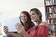 Two young female friends looking at tablet computer - RBF001568