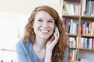 Young woman telephoning with smartphone at home - RBF001573
