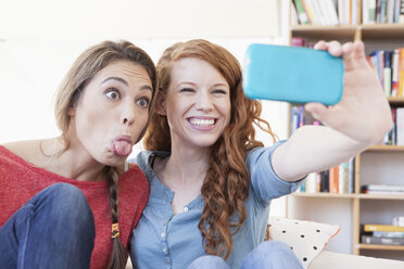 Two young female friends taking a picture of themseves with smartphone - RBF001576