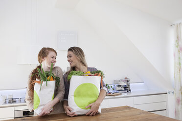 Two women holding shopping bags with purchases - RBF001579