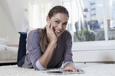 Woman at home lying on carpet and using tablet computer - RBF001505