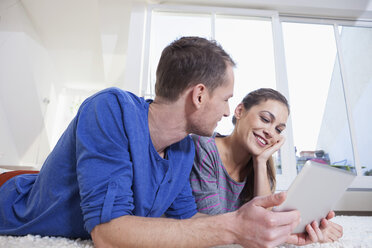 Couple at home lying on carpet and using tablet computer - RBF001502