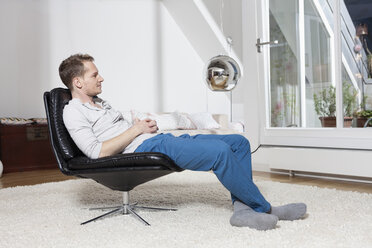 Man at home relaxing in armchair - RBF001501