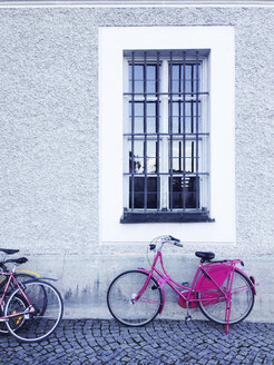 Pink bicycle in front of windows, old building, Munich, Bavaria, Germany - GSF000640