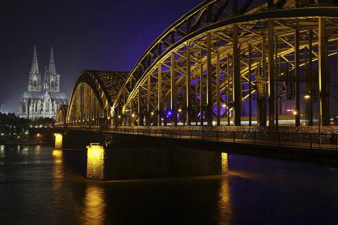 Germany, North Rhine-Westphalia, Cologne, lighted Cologne Cathedral and Hohenzollern Bridge at night - JATF000549
