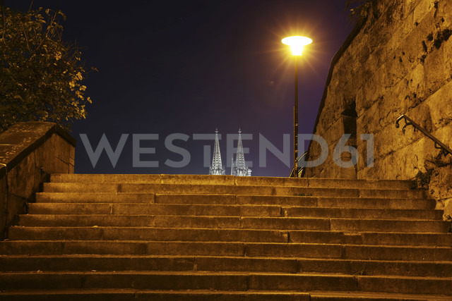 Germany, North Rhine-Westphalia, Cologne, lighted church spires of Cologne Cathedral and stairs to Hohenzollern Bridge at night - JATF000547