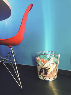 Laundry basket and chair being hit by ray of sunlight in front of a blue wall - MEAF000063