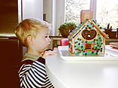 Little boy looking at gingerbread house on table - MEAF000036