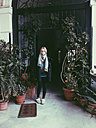 Young woman standing on balcony with plants, Palermo, Sicily, Italy - MEAF000106