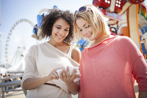Germany, Herne, Two young women at the fairground using smart phone - BGF000060
