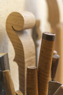 Tools and scroll of a violin in a violin maker's workshop - TCF003817