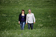 Young couple walking hand in hand on a meadow - SL000370