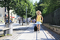 Girl with pulling suitcase running on sidewalk - VTF000057
