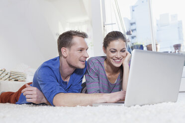 Couple lying on carpet at home using laptop - RBF001499