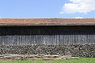 Germany, Bavaria, Toelzer Land, Stack of wood in front of barn - CRF002565