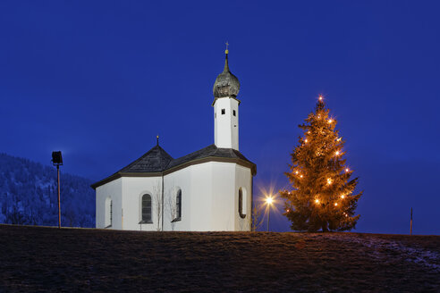 Austria, Tyrol, Achenkirch, view to Church of St. Ann and lighted christmas tree by night - GFF000401