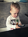 Toddler child playing with real phone, Goettingen Germany - ABA001162