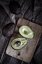 Sliced and whole avocados on chopping board and wooden table - SBDF000461