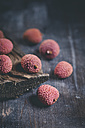 Lychees and board on dark wooden table - SBDF000439