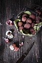 Wire basket, knife and whole and peeled lychees on dark wooden table - SBDF000441