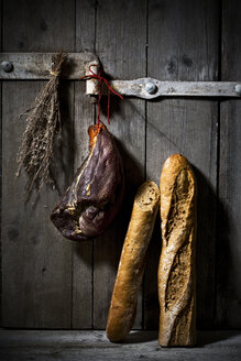 Smoked ham and onion baguette on wooden door - MAEF007643