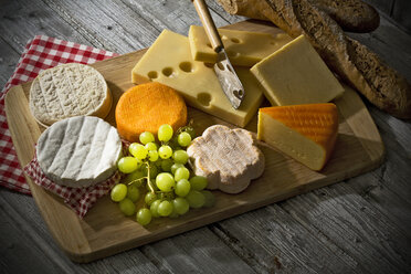 Cheese platter, different cheese, french cheddar, french soft cheese, french sheep cheese, camembert, emmentaler, and austrian mountain cheese and wholemeat baguette on wooden board - MAEF007648