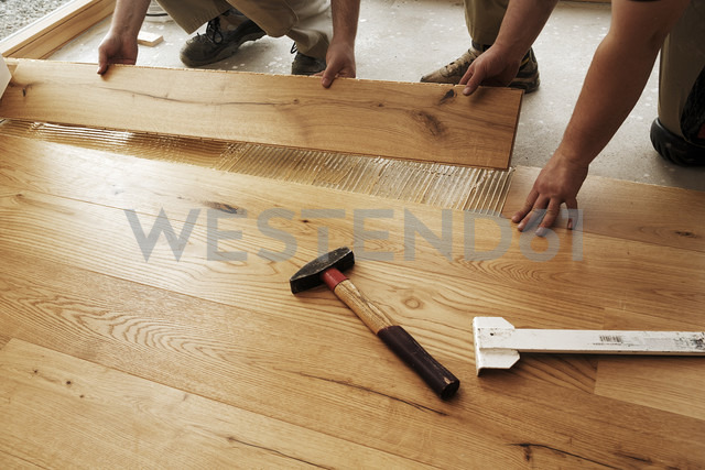 Two men laying finished parquet flooring, close-up - BIF000303 - Ingo Bartussek/Westend61