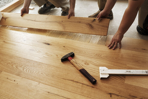Two men laying finished parquet flooring, close-up - BIF000303