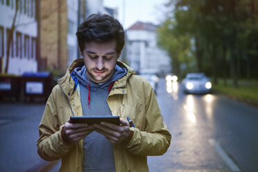Germany, North Rhine-Westphalia, Cologne, young man standing on a street using digital tablet - FEXF000065